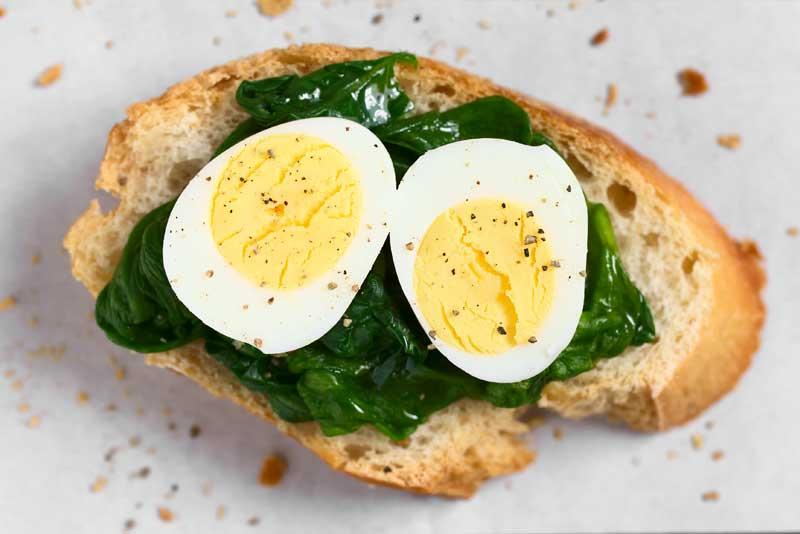 Huevo cocido sobre una rebanada de pan y espinacas