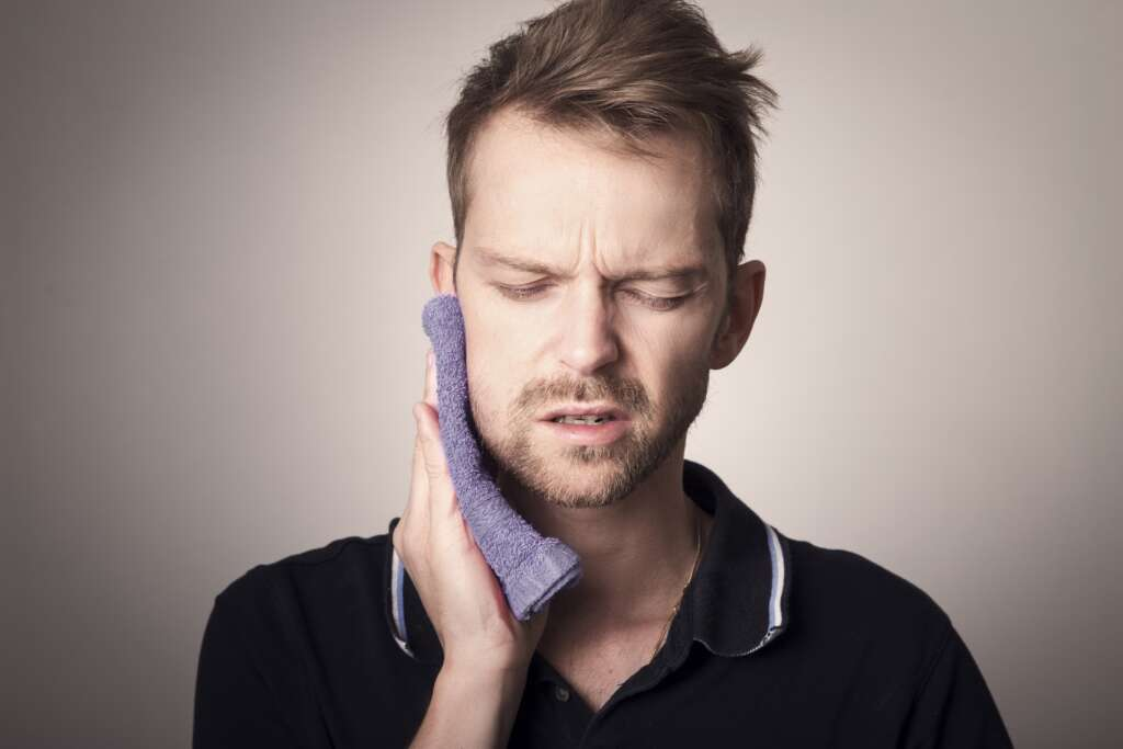 toothache man using a warm cloth to soothe pain in the face