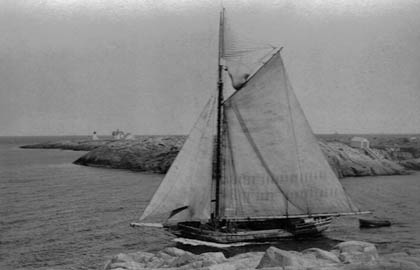 """Granite sloop Albert Baldwin sailing through the """"gap"""" in 1920. Boat house on the right built in 1867 and eliminated in 1937."""
