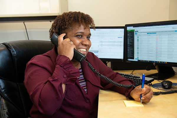 A NetCenergy employee providing managed IT service on the phone with a client