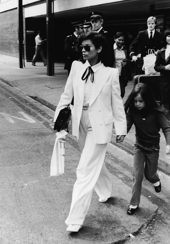 Nicaraguan-born model Bianca Jagger wears a double-brested white suit as she and her daughter Jade walk across the street in front of a group of policemen in London, May 4, 1979. (Photo by Express Newspapers/Getty Images)