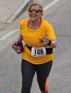 Deb at the finish line of the Red's Shoe Barn 5 Mile Race
