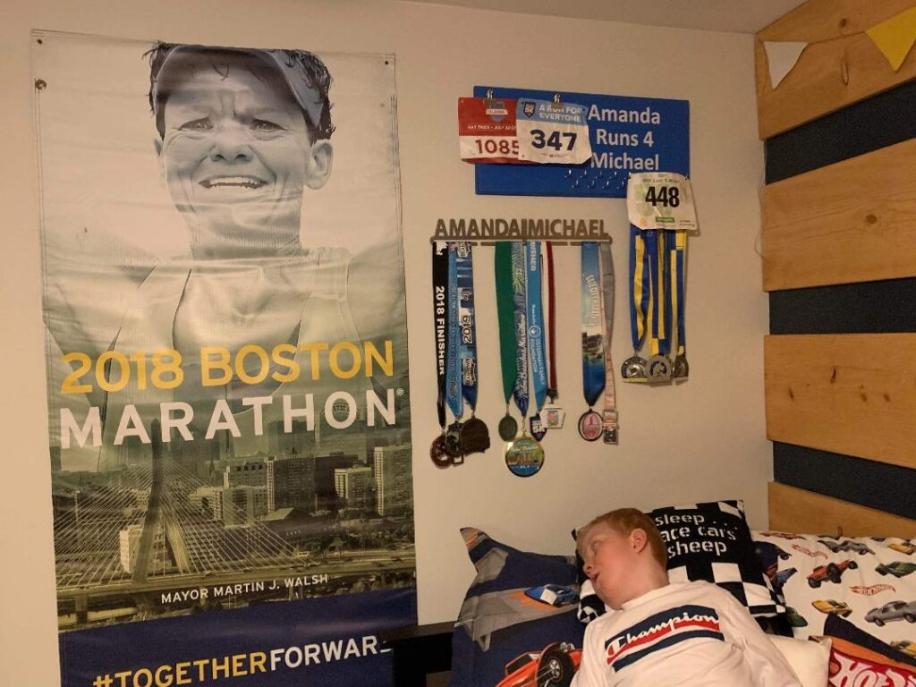 Michael at home with a poster of Amanda and the medals she has sent him on the wall.