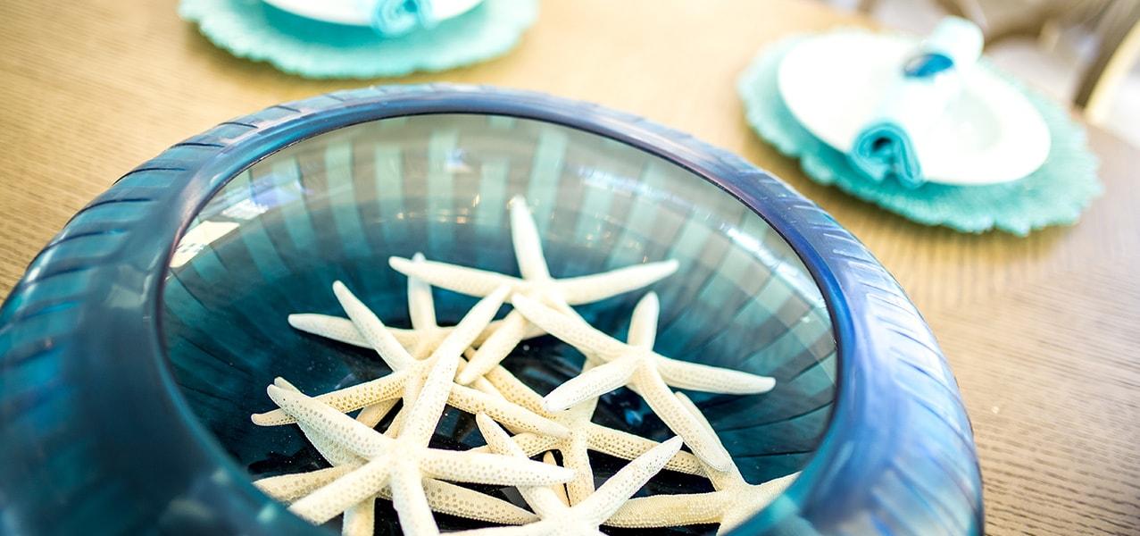 Sugar Beach Interiors, Miramar Beach, Florida. Decorative blue bowl filled with white starfish