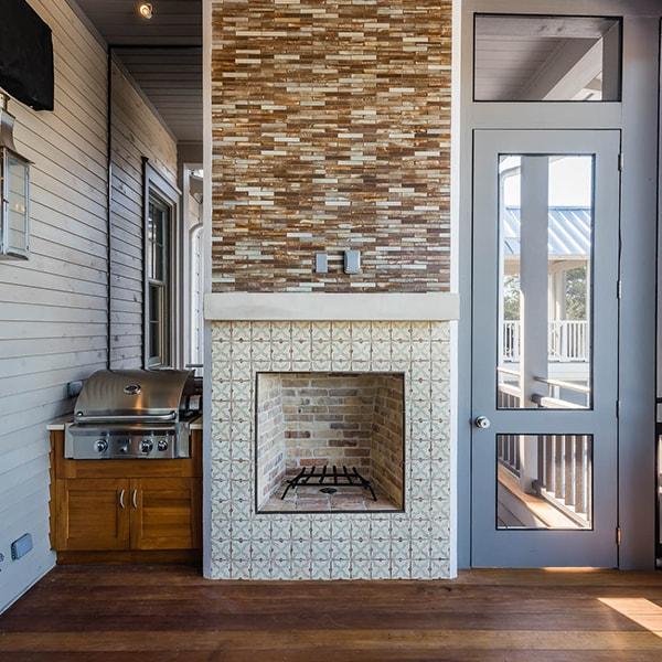 Sugar Beach Interiors, Miramar Beach, Florida. Outdoor patio with fireplace and grill