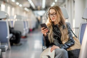 Woman Browsing Websites on her Cell Phone while Traveling