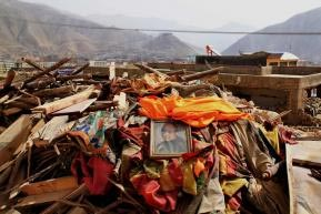 A photo of the Dalai Lama placed on top of ruins in Yushu.