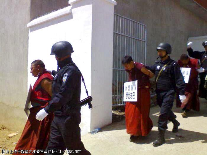 monks with placards around their necks are lead away from their monastery