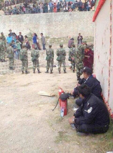 The site of Shichung's self-immolation in Gomang, Ngaba, showing police with fire extinguishers and troops.