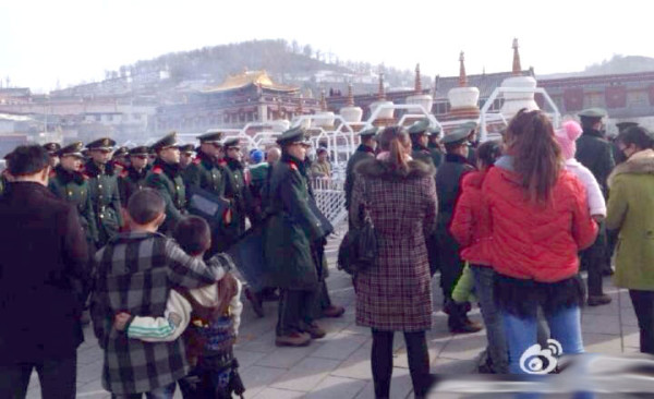 Pilgrims wait for police at the entrance to Kumbum.