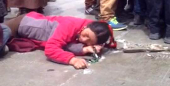 A Tibetan woman lies on the road as part of a sit-in protest at the mine in Lhagang.