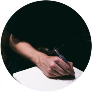 Man's hand writing in notebook