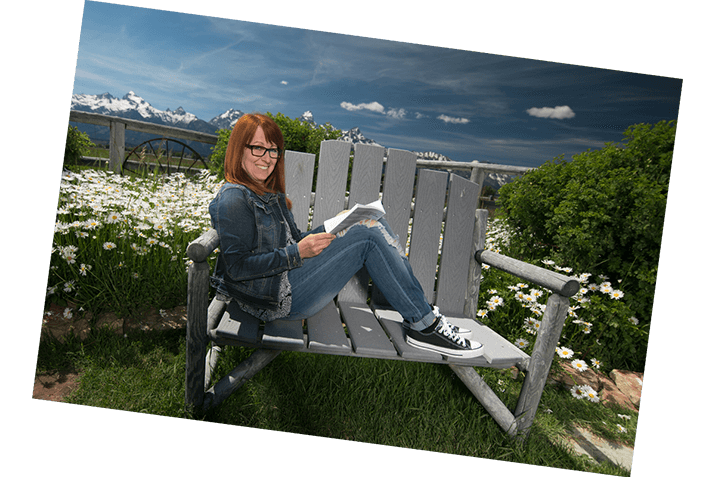 Woman reading with Grand Tetons in the background