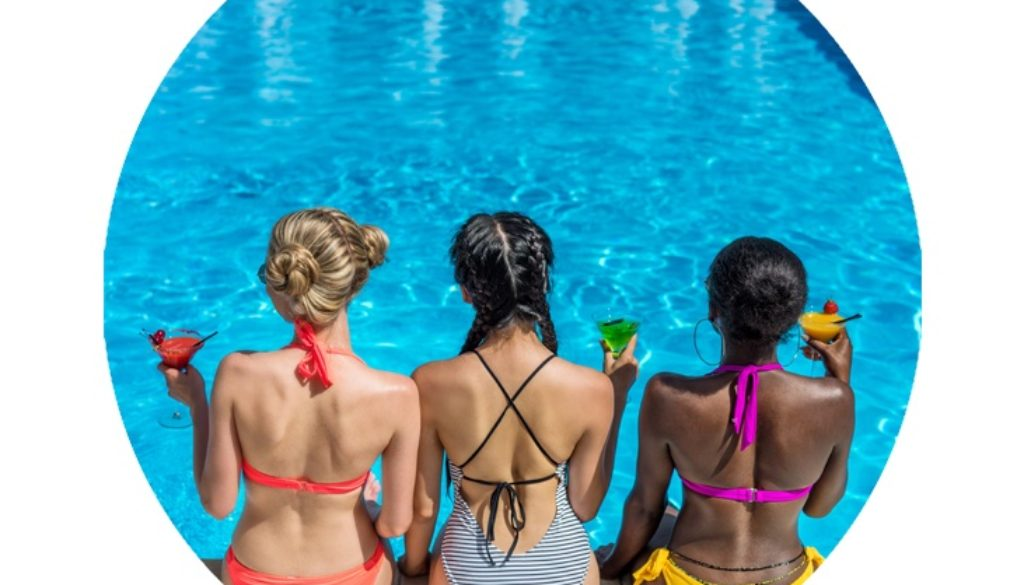 3 women with martinis sitting by a swimming pool