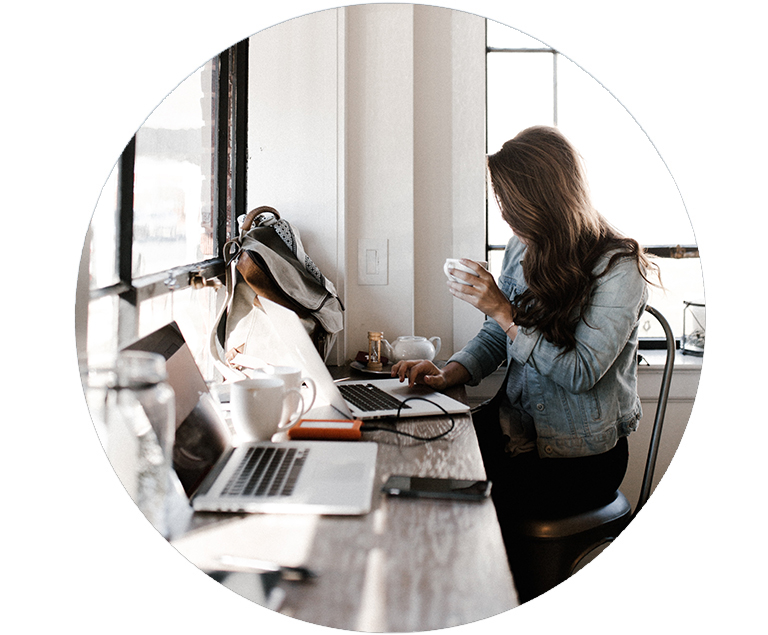 Woman sitting at counter writing on laptop and sipping coffee