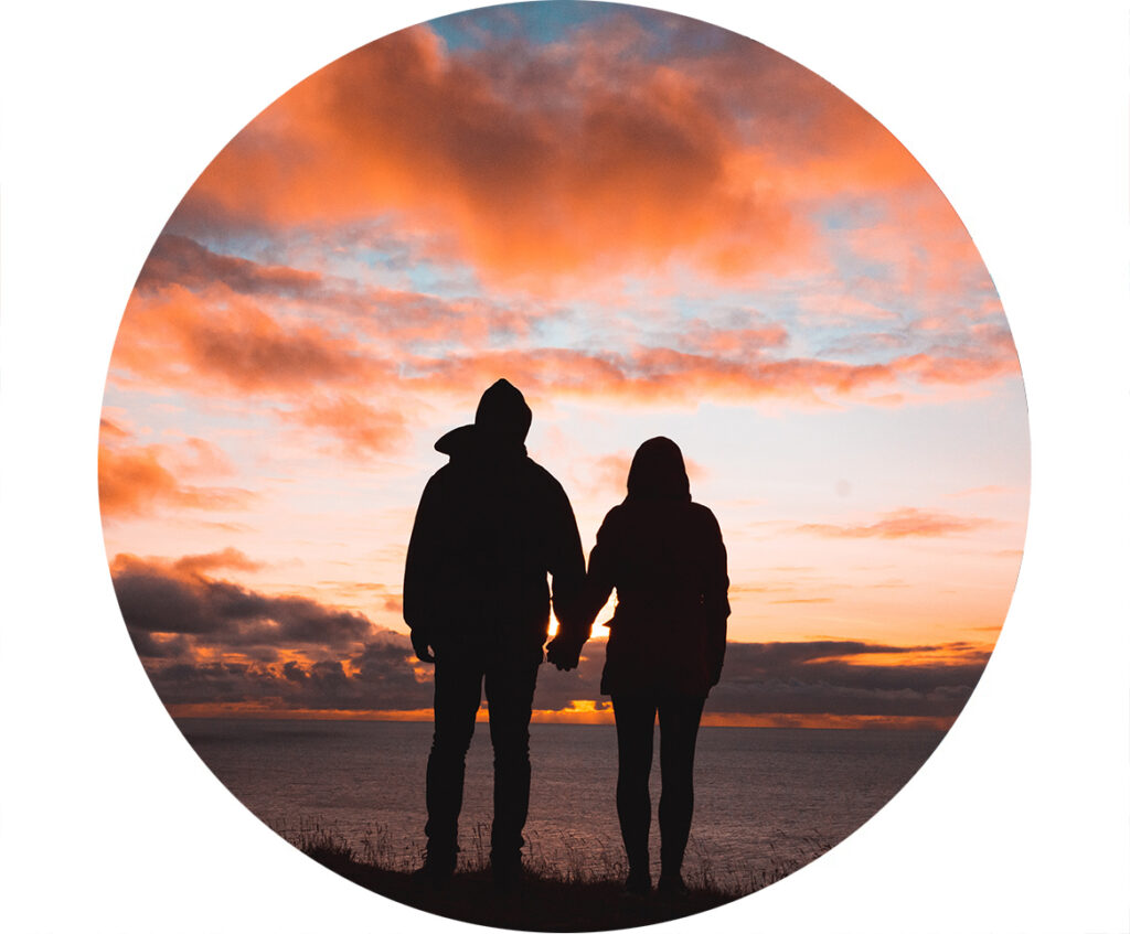 Silhouette of couple holding hands watching sunset