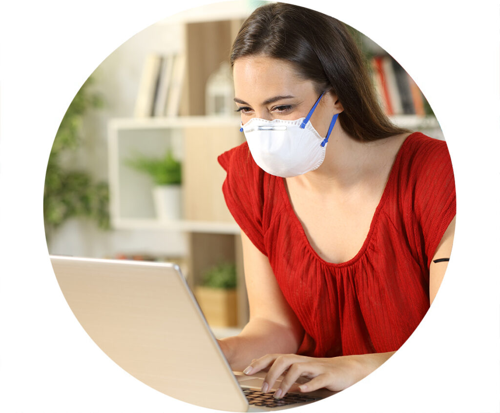Woman wearing N95 Mask typing on laptop
