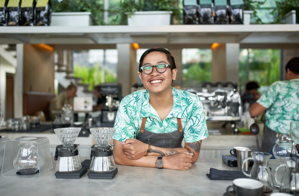 Lifestyle portrait of young confident balinese barista, wearing apron and smiling at camera in modern and trendy hipster cafe serving organic fair-trade coffee in a bright positive environment with tropical plants