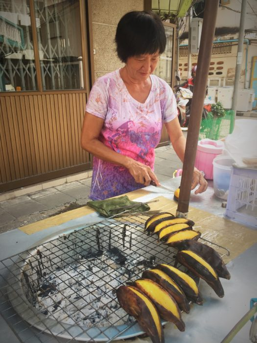 Travel like a local: Relishing street food (grilled ripen banana) in Bangkok, Thailand.