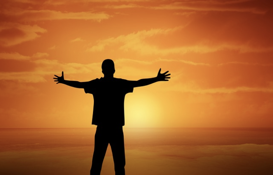 Man with outspread arms facing sun