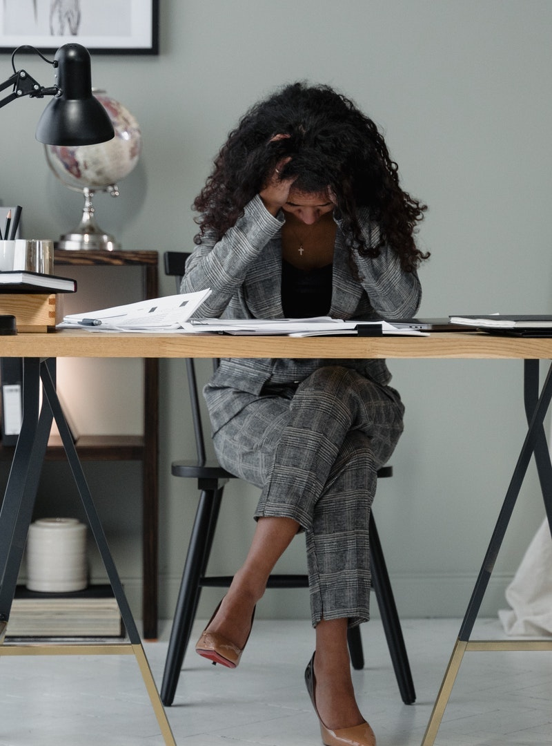 Black woman sits at desk with her head down disappointed about her abusive relationship with money