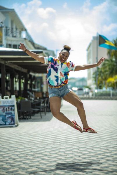 This Bahamian Gyal blogger, Rogan Smith jumps in front of the Bahamian flag in Downtown, Nassau, Bahamas.