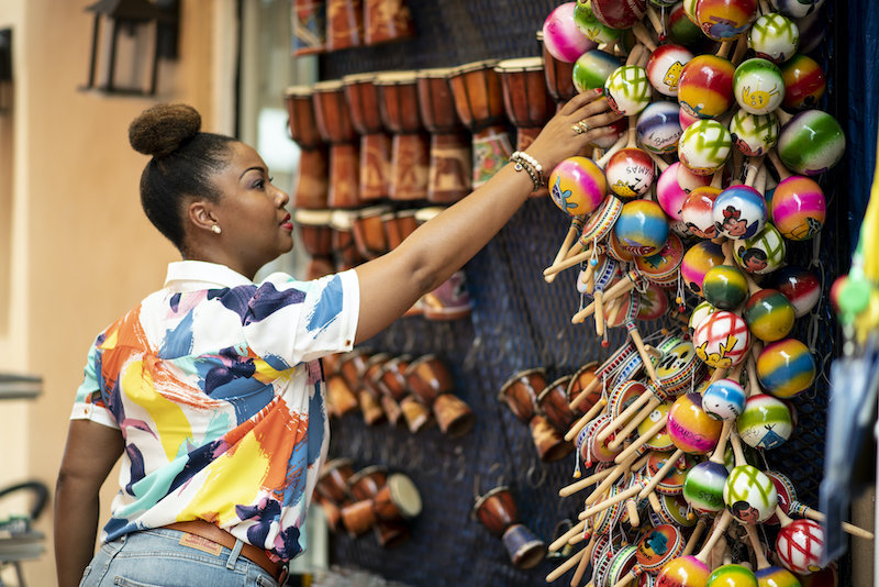 Bahamian Blogger, Rogan Smith buys a souvenir in Downtown Nassau. The Bahamas is now open for travel.