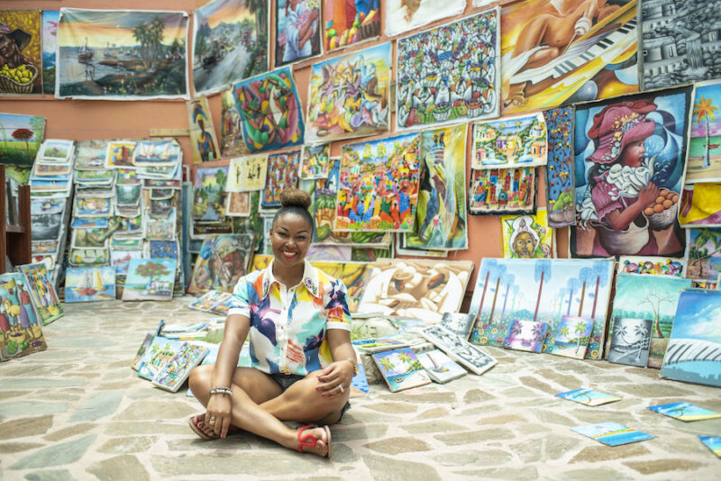 Bahamian Blogger, Rogan Smith is surrounded by local art in Downtown Nassau. The Bahamas will reopen for travel on July 1.