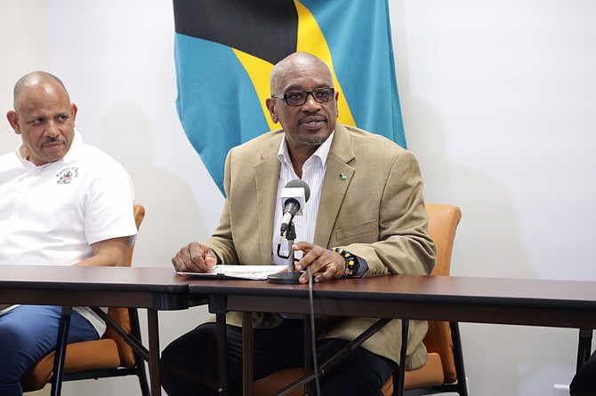 Dr. Duane Sands (left) listens to Prime Minister Dr. Hubert Minnis as he stresses that The Bahamas will not take chances with the deadly COVID-19. (Photo/courtesy of The Tribune)