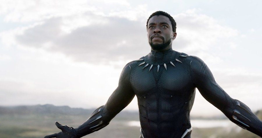 Actor Chadwick Boseman poses in his Black Panther costume. His arms are outstretched.
