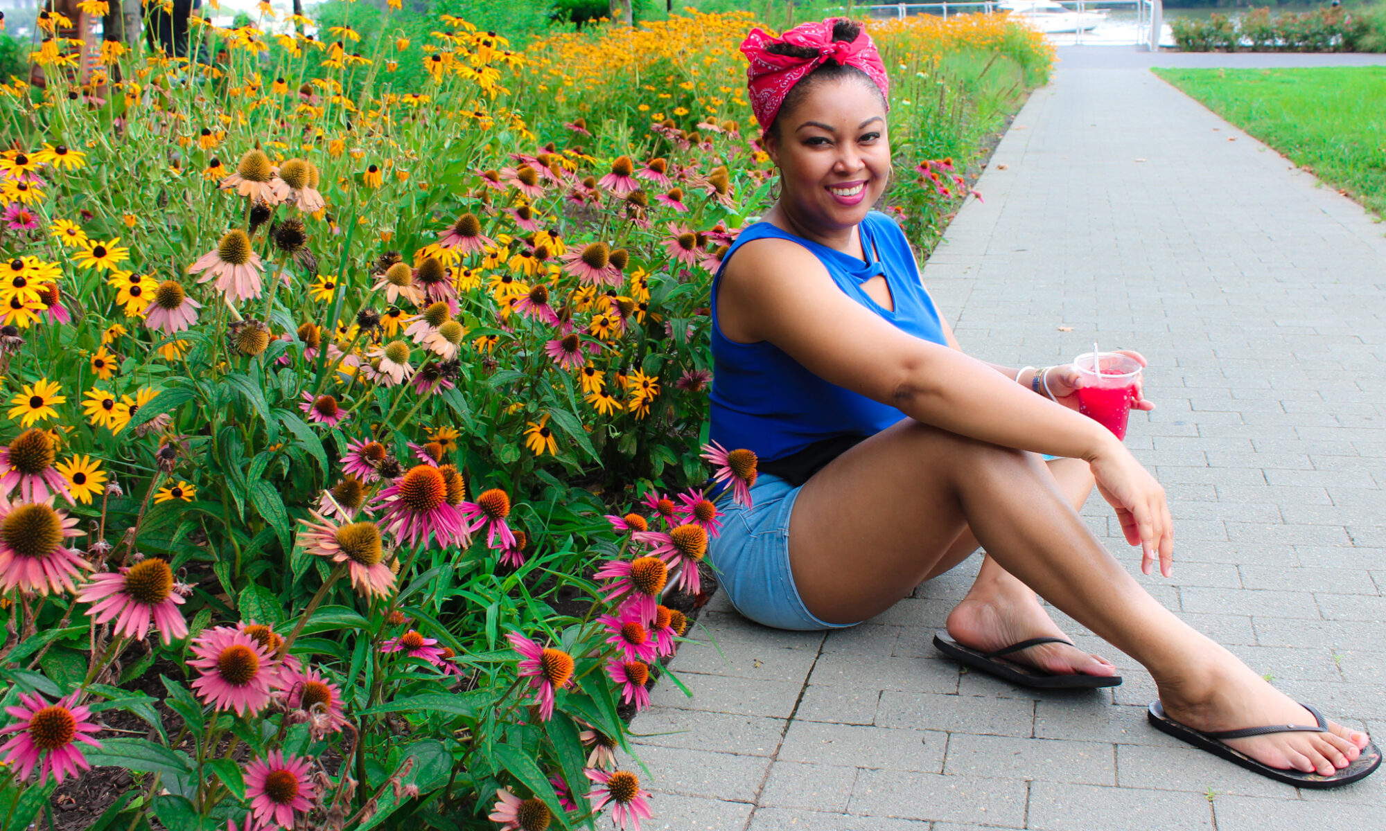 DC blogger Rogan Smith of This Bahamian Gyal sits among flowers in Georgetown, DC
