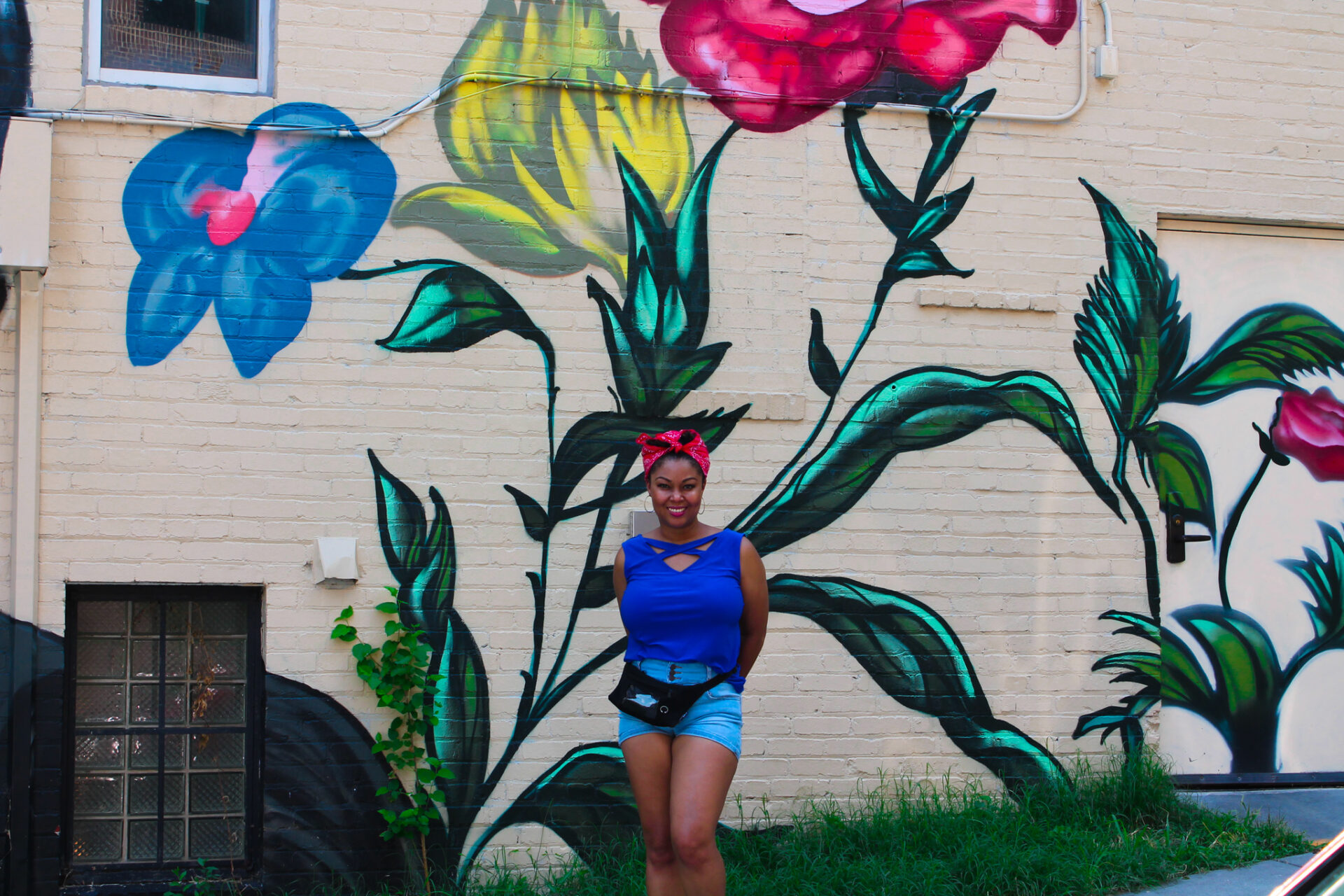 This Bahamian Gyal blogger, Rogan Smith poses in front of a flower mural in Georgetown, DC.