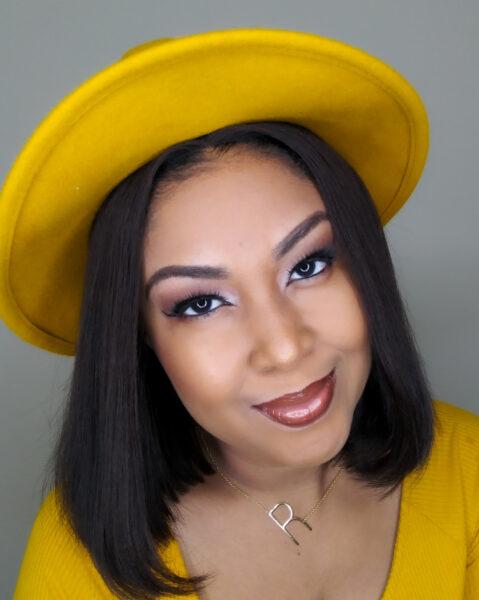 Black light skinned blogger wears a mustard fedora and a mustard shirt