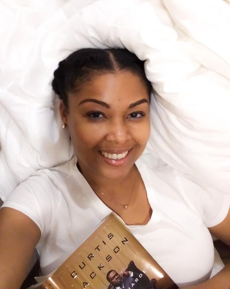 black blogger Rogan Smith holds 50 Cent book Hustle Harder Hustle Smarter