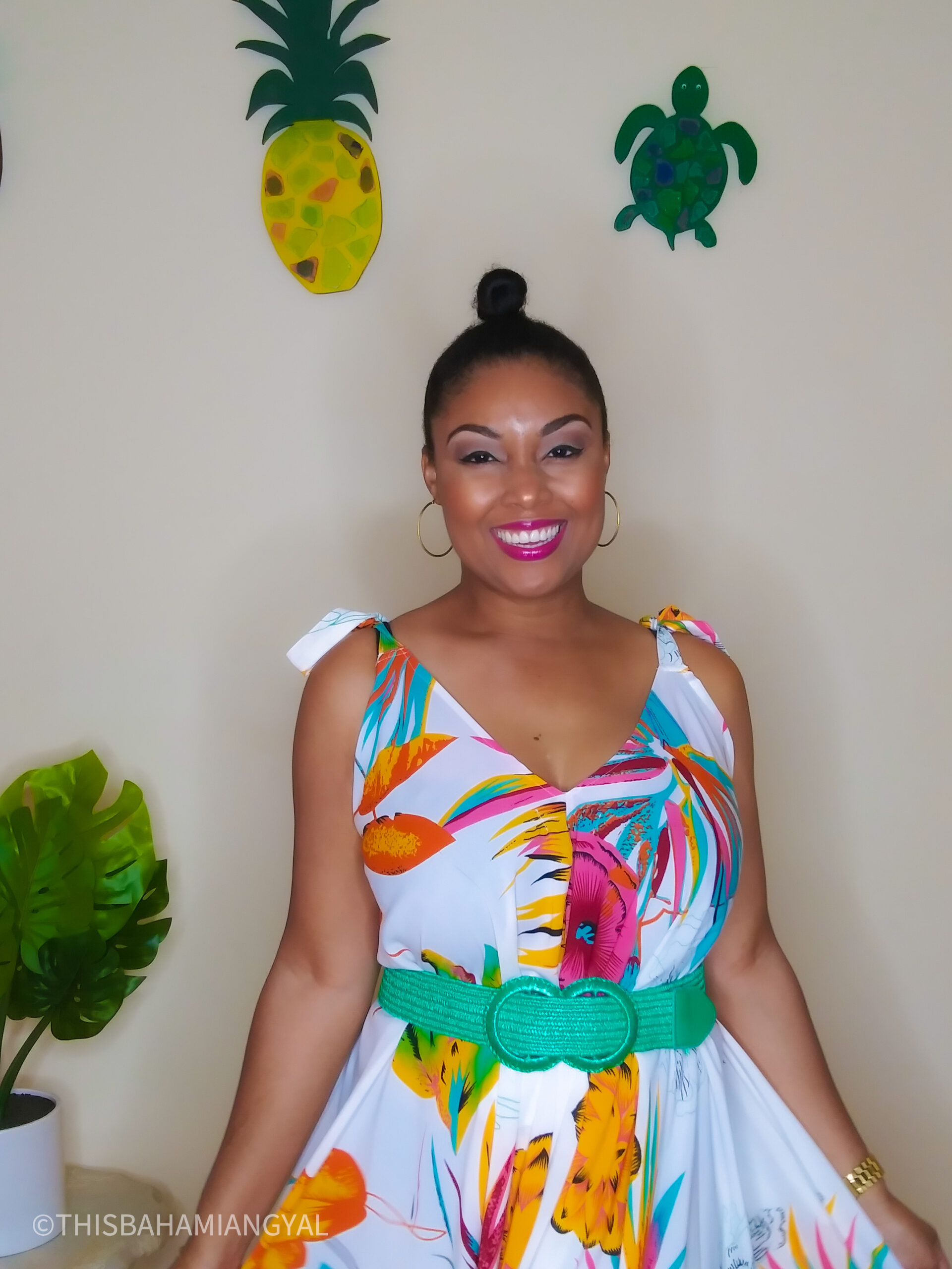 This Bahamian Gyal lifestyle and beauty blogger, Rogan Smith poses for the camera. She's wearing a colourful tropical romper with a green belt.