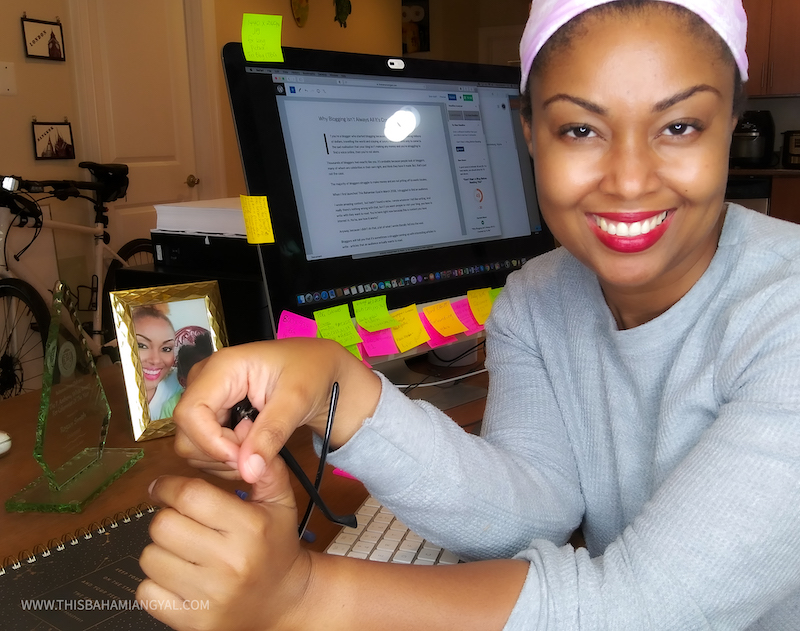 Black female blogger sits behind computer desk and smiles at camera.