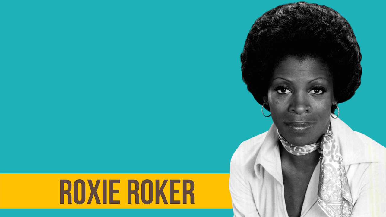 Image of actress Roxie Roker wearing a scarf around her neck and a white shirt.