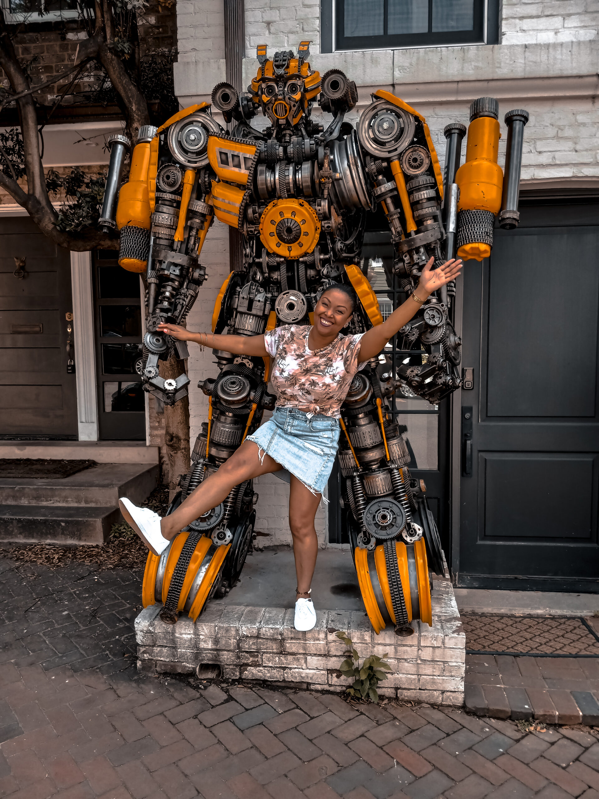 DC blogger Rogan Smith of This Bahamian Gyal poses in front of the Transformers house in Georgetown DC. She is shown in the picture with the robot, Bumblebee.