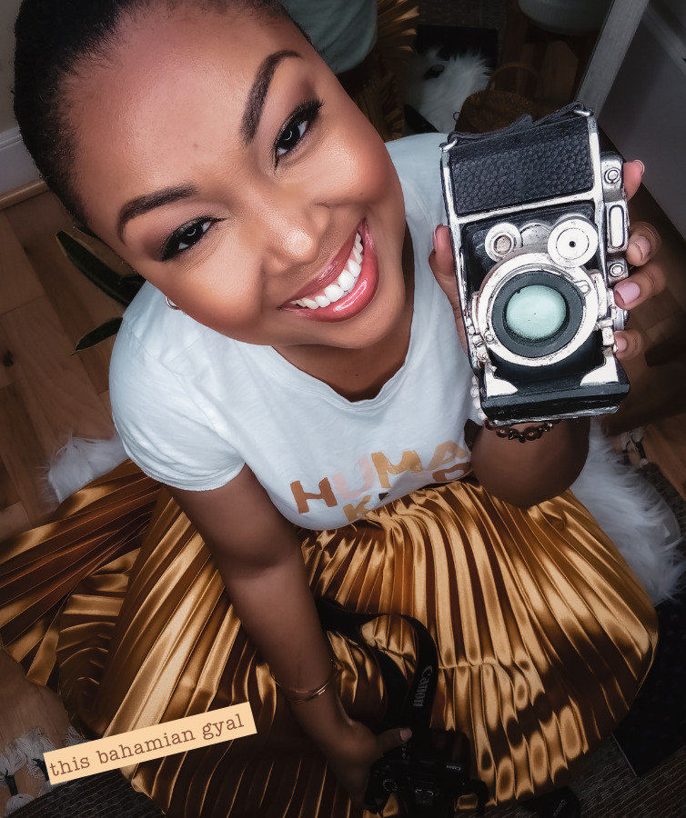 black woman holds camera on her blog where she shows how to take photos of yourself by yourself