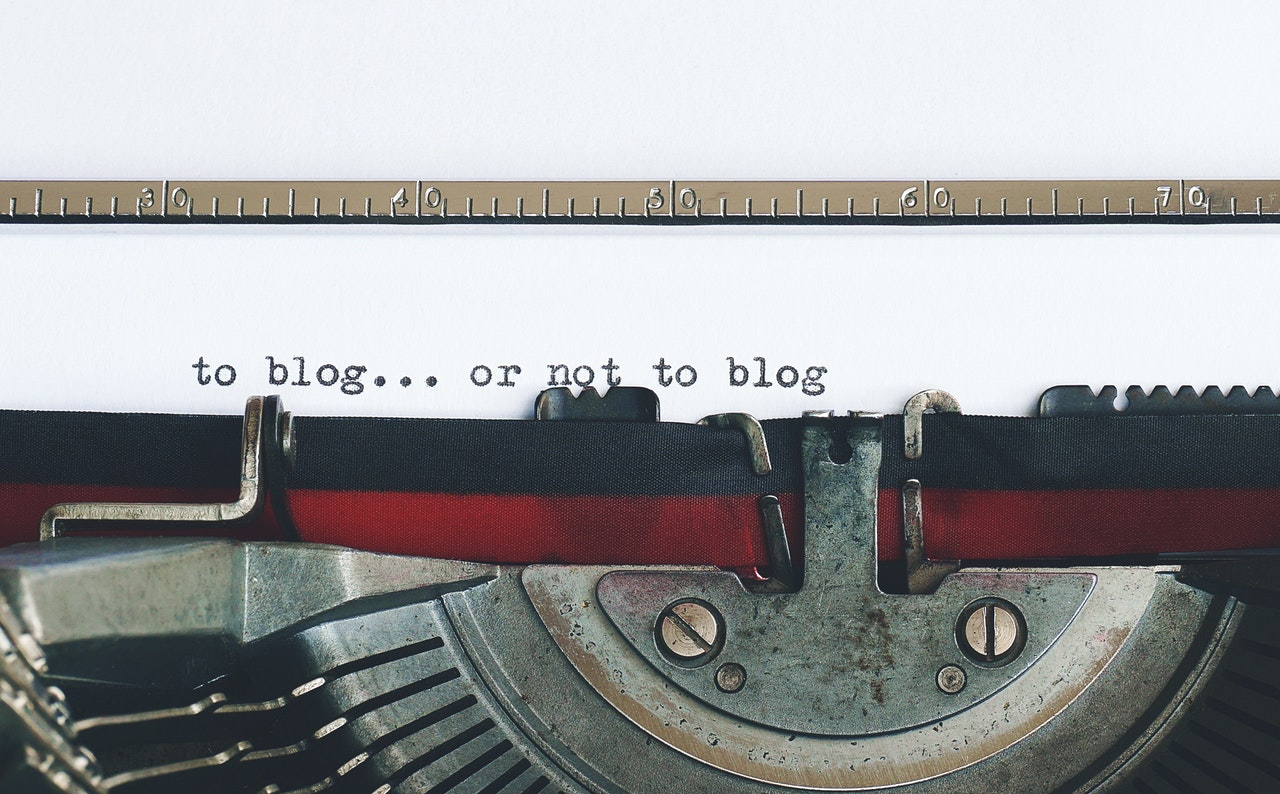 Photo of a typewriter with the words, blog or not to blog written on a white sheet of paper