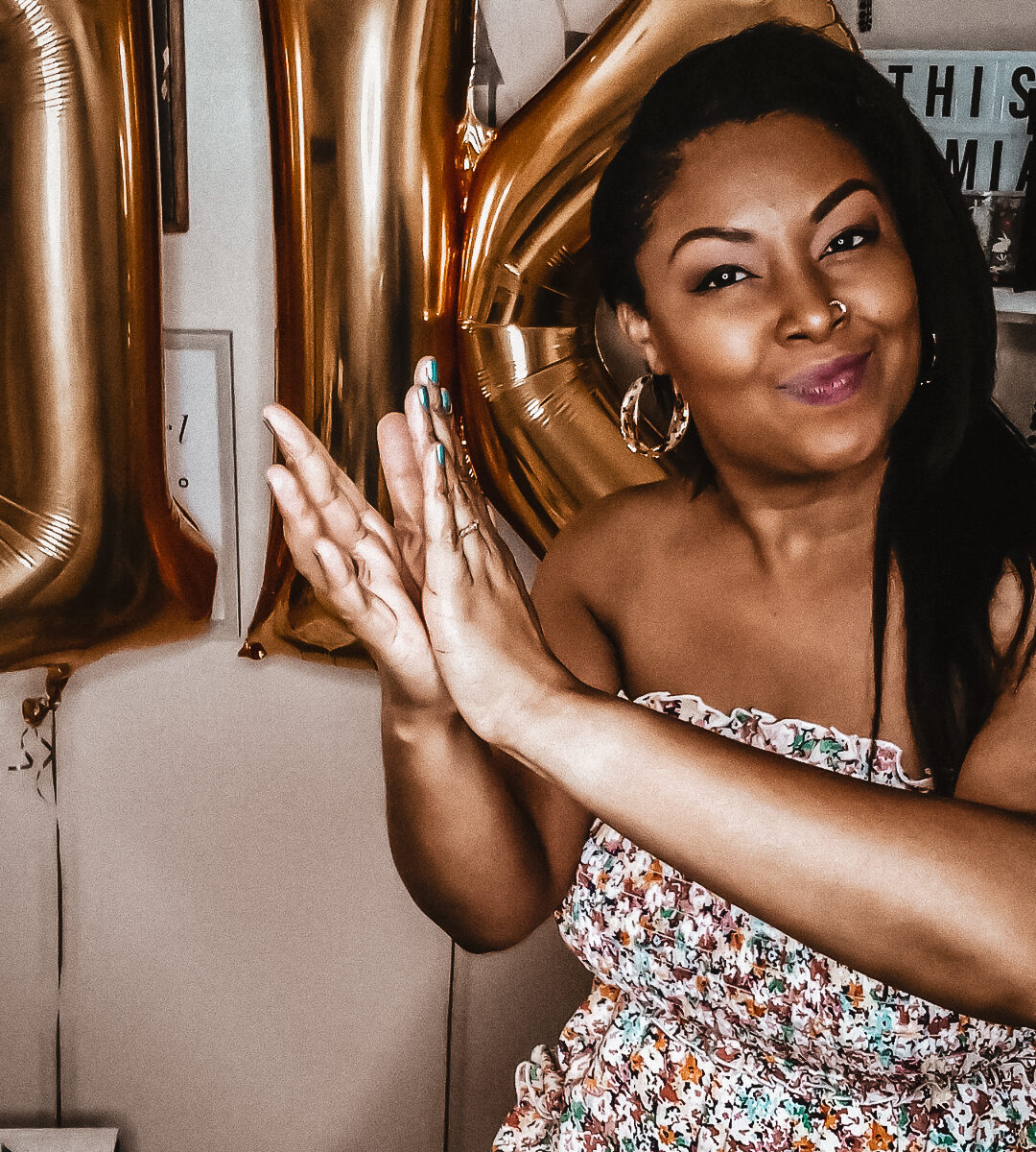 Black woman with light skin smiles into the camera and claps her hands. A ballon sign that spells out 1K is in the background.