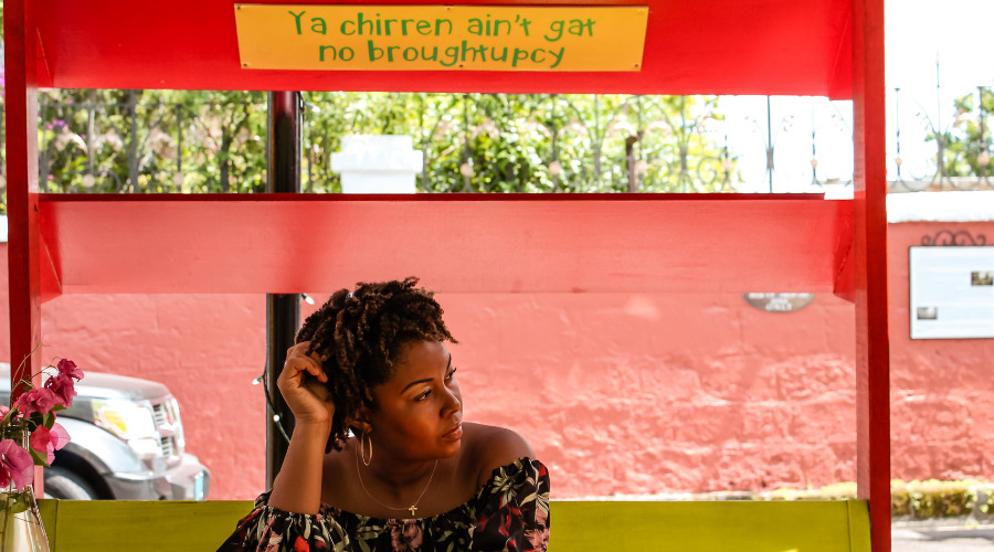 Image of a black woman sitting on a bench in front of a sign with the Bahamian words, ya chirren ain't gat no broughtupcy.