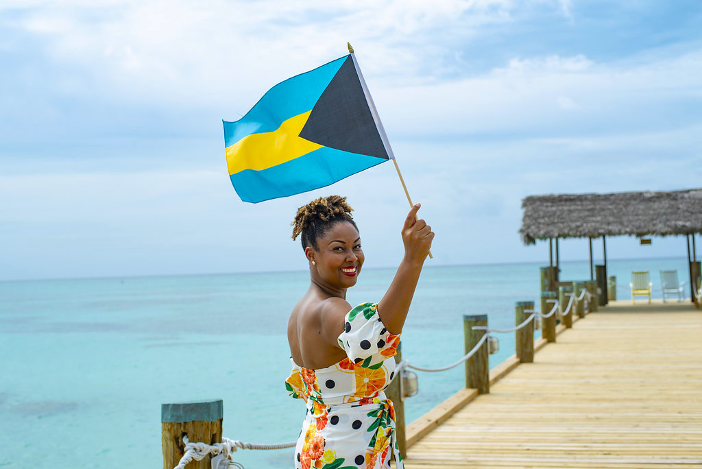 Black Bahamian blogger Rogan Smith poses on a dock holding a Bahamian flag in her right hand