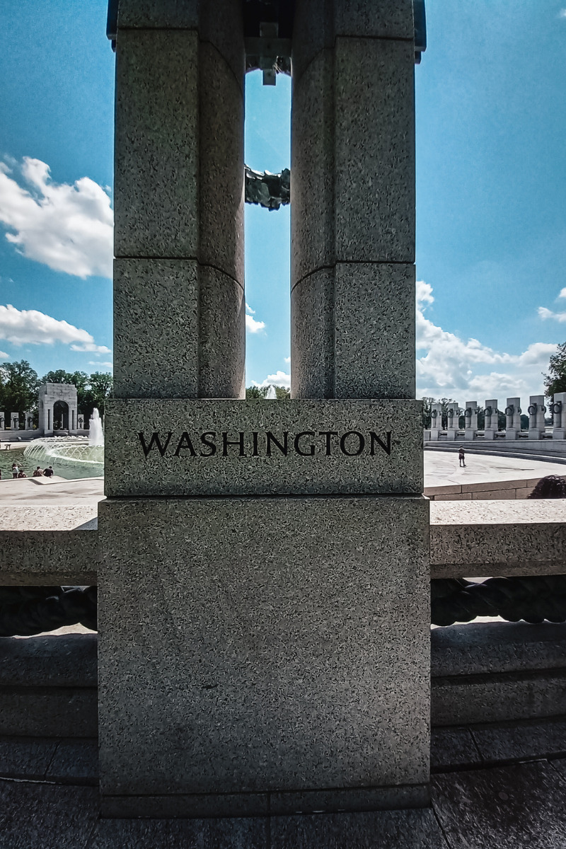Image of the World War II memorial Washington DC. The word Washington is engraved in stone.