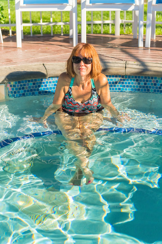 Woman with sunglasses sitting in hot tub