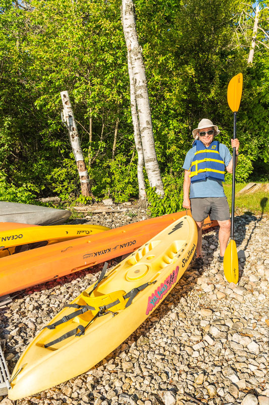 Man in life vest holding kayak handle and paddle while standing on shoreline