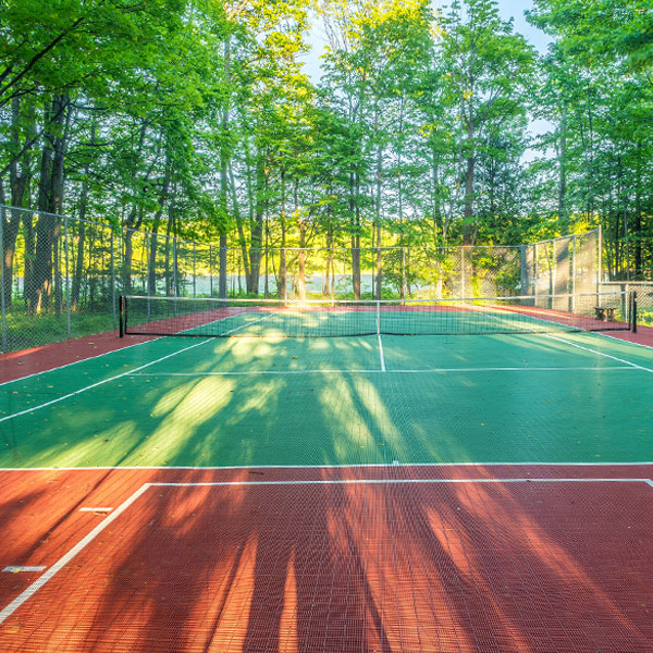 Sunlight through trees hitting the tennis courts at Shallows Resort