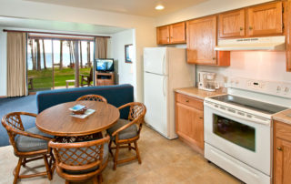 Beachhouse interior with full kitchen, table, chairs, sofa, TV and view of the bay