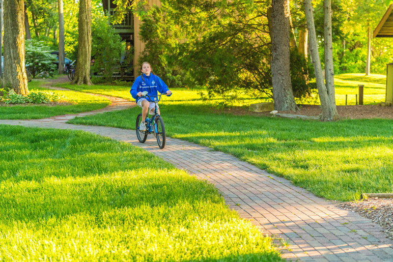 Small child riding bike on winding path on Shallows Resort property