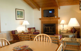 Interior of Shallows Cottage including couch, chairs, fireplace and large screen TV